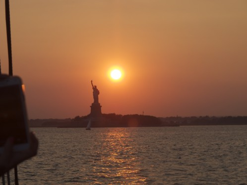 The sun going down over New York Harbor next to the Statue of Liberty.